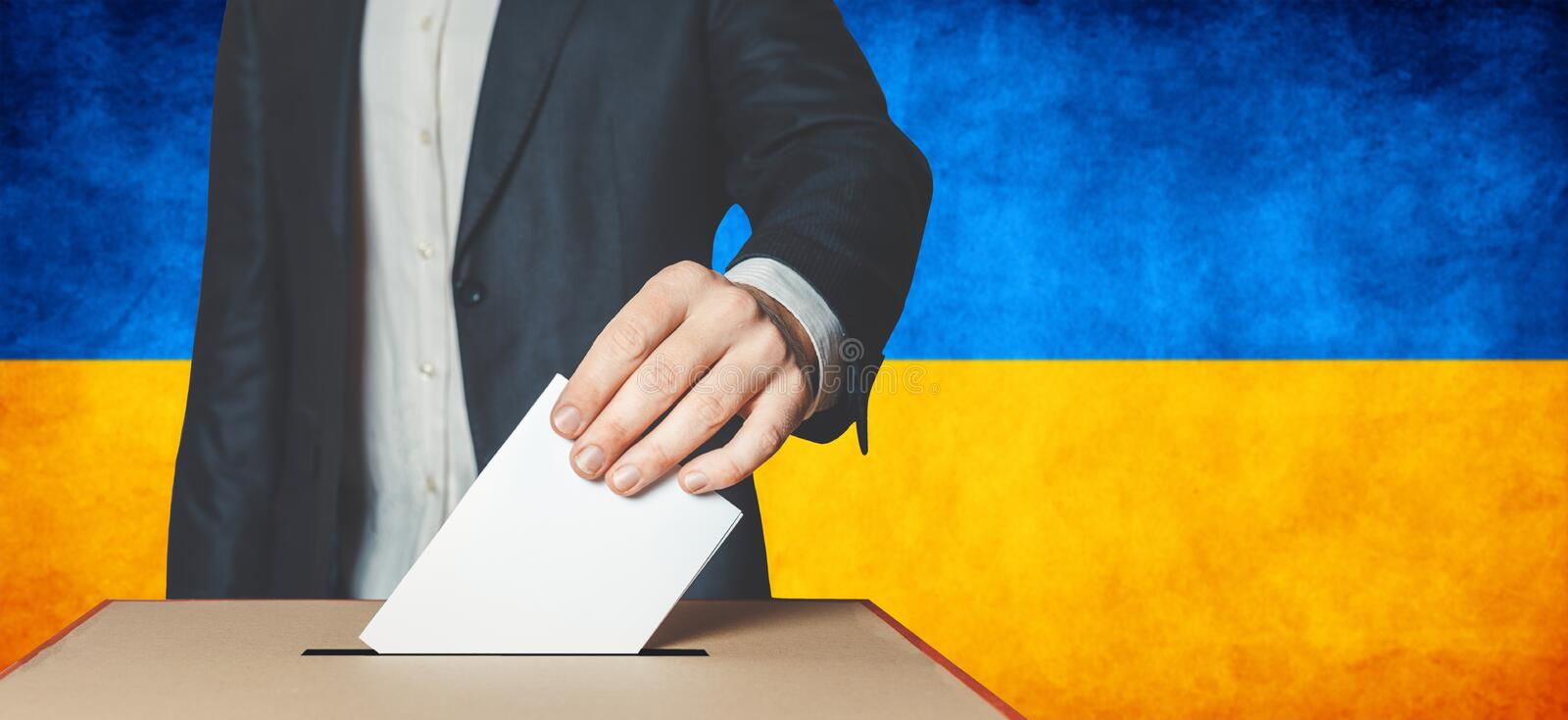 Elections in Ukraine, political struggle. Democracy, freedom and independence concept. Man Voter Putting Ballot In to Voting box. Elections in Ukraine, political royalty free stock image