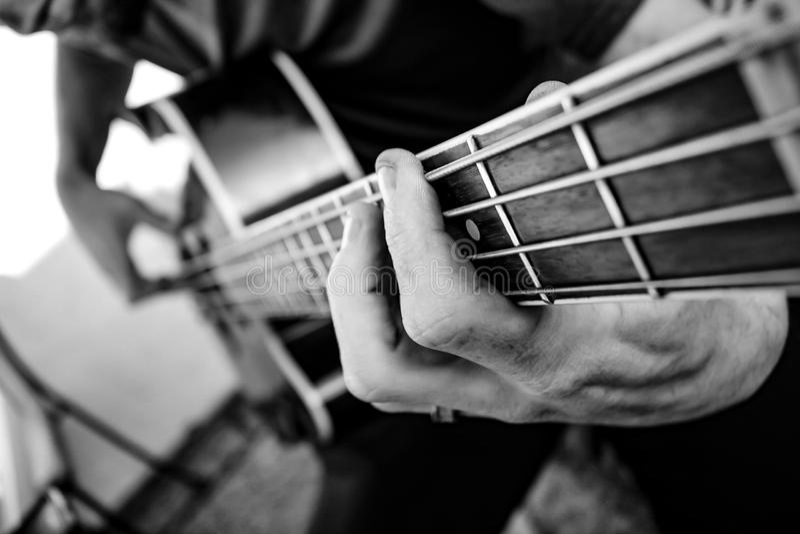 Electric Acoustic Bass Guitar. Selective focus man playing an accoustic bass guitar stock photo
