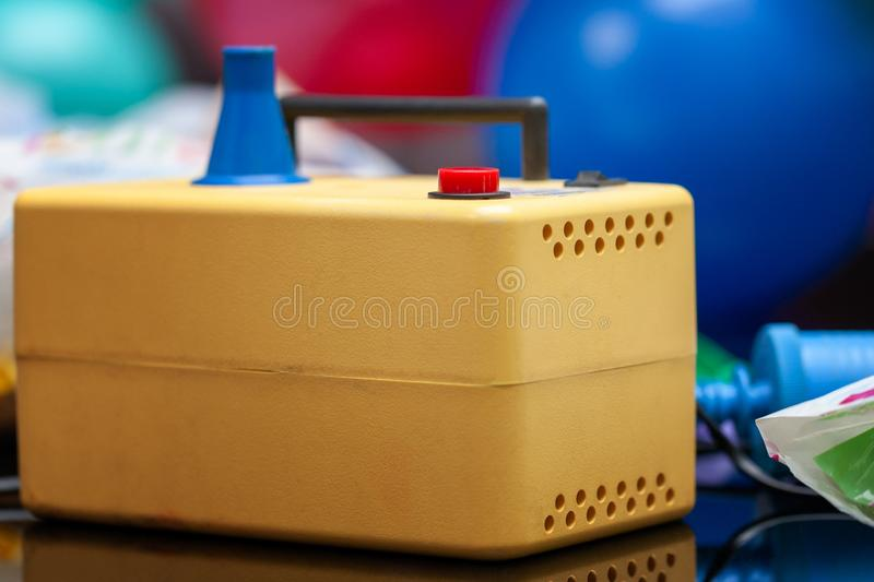 Electric air pump to blow balloons. preparation and decoration to celebrate. blurred balloons at background stock photos