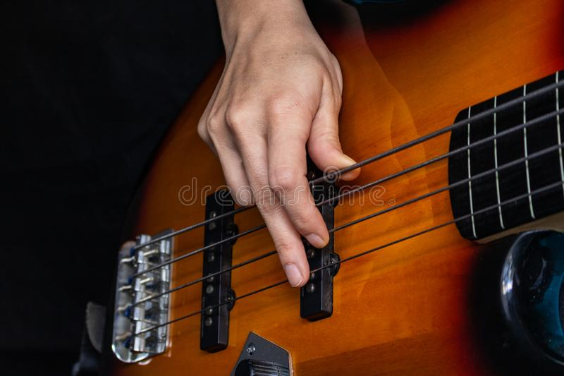 An electric bass guitar being strum royalty free stock photography