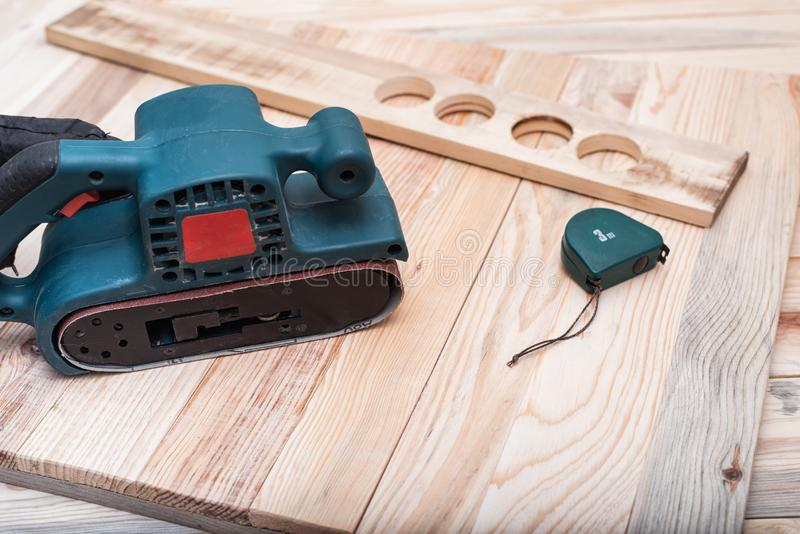 Electric belt sander, measuring tape and workpiece lying on a light brown wooden table. Woodworking, sanding machine. Close up.  stock photography
