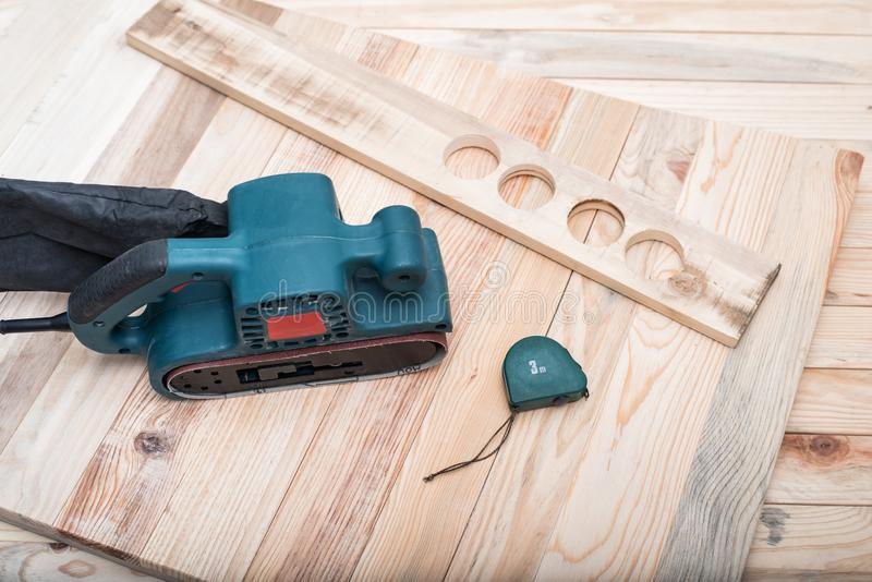 Electric belt sander, measuring tape and workpiece lying on a light brown wooden table. Woodworking, sanding machine.  royalty free stock images
