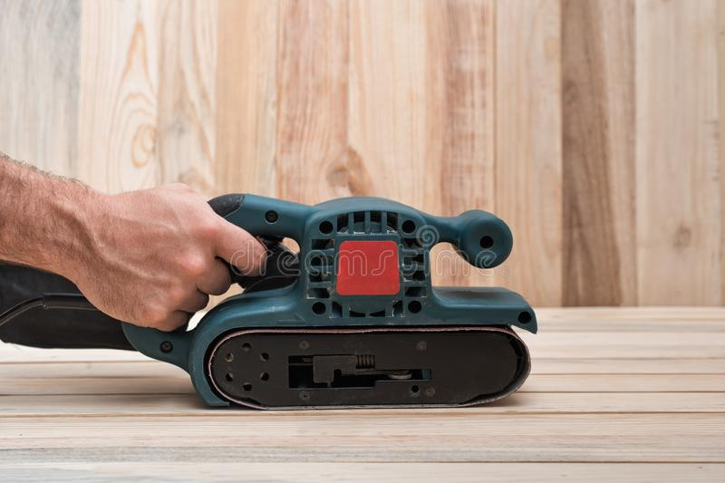 Electric belt sander, sanding machine in male hand. Processing of workpiece on light brown wooden table. Side view, close up.  stock images