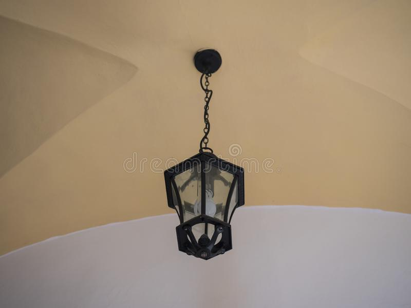 Electric black vintage lamp or lantern hanging on a chain under a vaulted yellow and white ceiling. Copy space.  royalty free stock photos