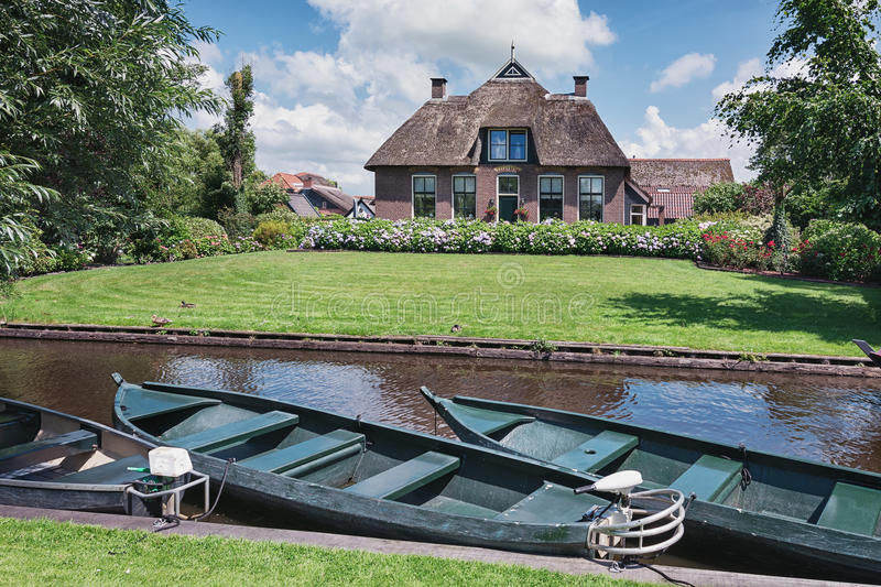 Electric boats moored in the channel. Moored electric boats in the canal in the Dutch village Giethoorn and on the background a thatched house with a garden stock image