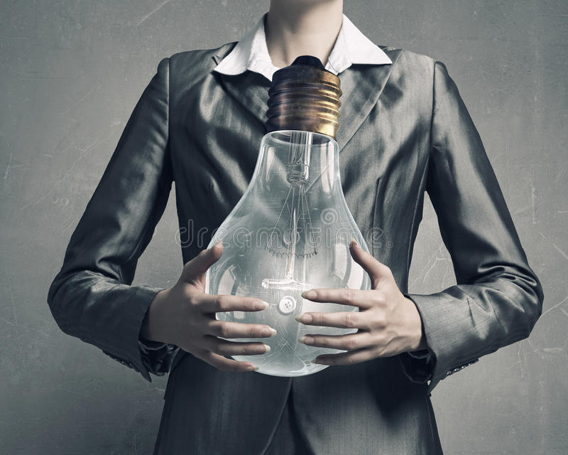 Electric bulb in woman hand . Mixed media royalty free stock photography