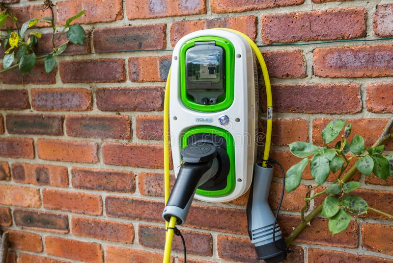 Wall mounted electric car charger. Electric car charger mounted on brick wall stock images