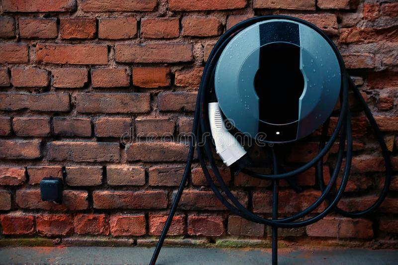 Electric car charger on red brick wall royalty free stock images