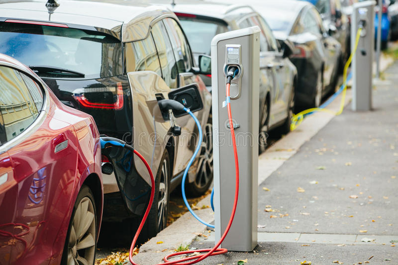 Electric car. Charging on parking station on city street stock images