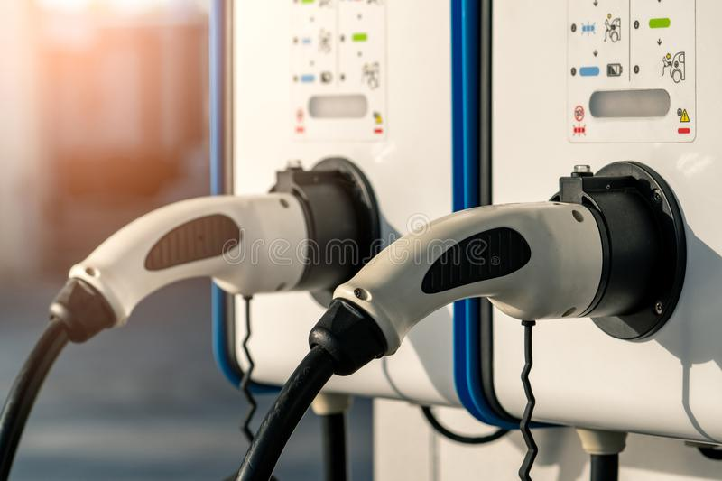 Electric car charging station. Plug for vehicle with electric motor. Coin-operated charging station. Clean energy power. royalty free stock photography
