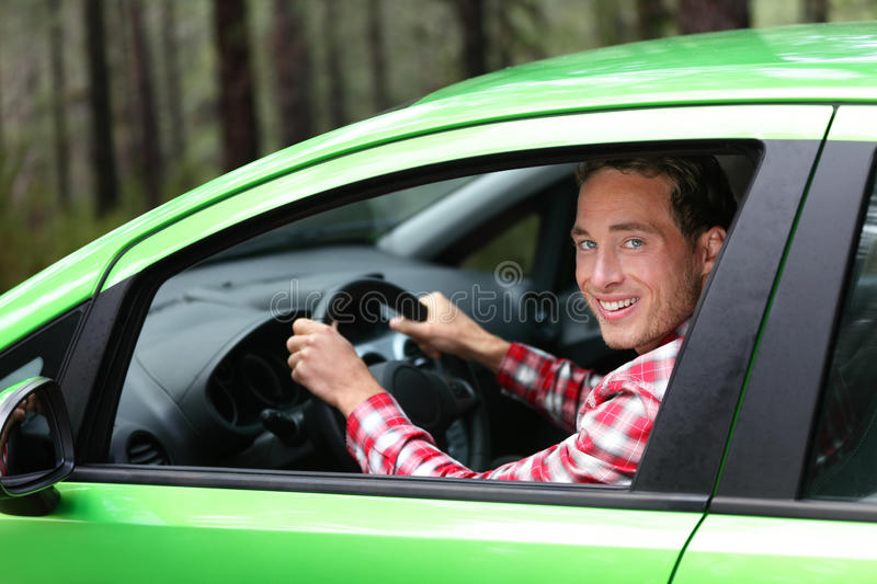 Electric car driver - green energy biofuel concept. Male behind wheel. Man driving new vehicle in cheerful in nature forest. Young male driver looking at royalty free stock images