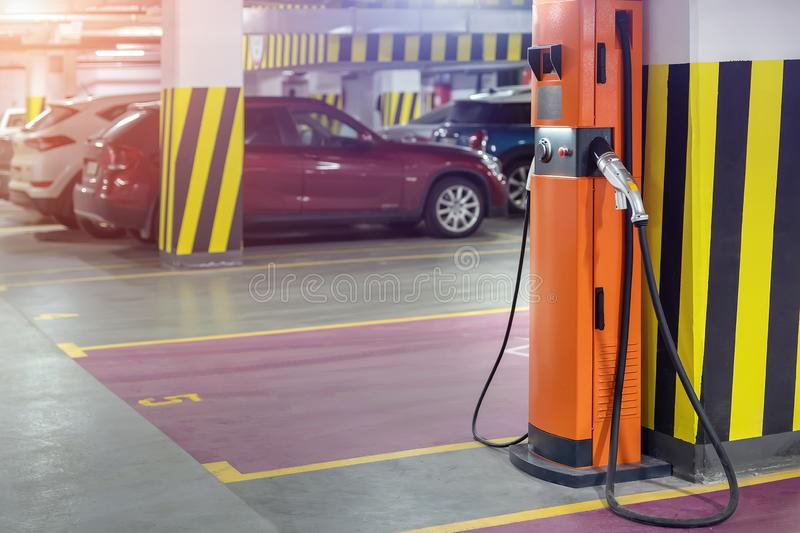 Electric car fast charging station at indoor underground parking. Power supply point network for hybrid electric car royalty free stock photography