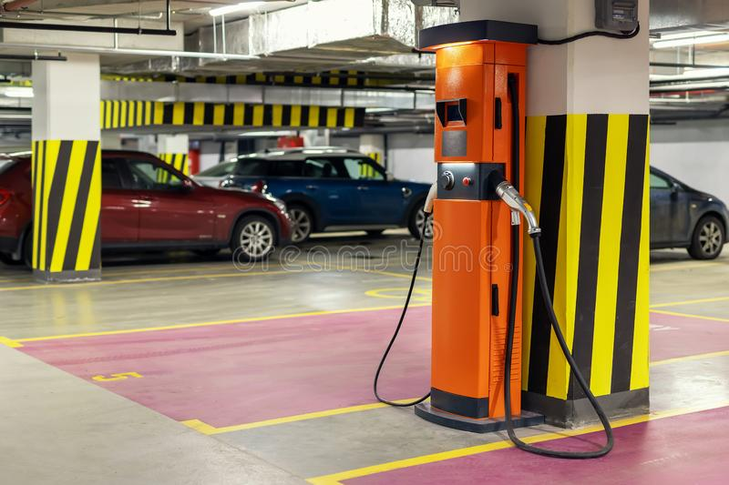 Electric car fast charging station at indoor underground parking. Power supply point network for hybrid electric car. Charging battery. Eco green energy stock image