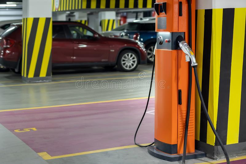 Electric car fast charging station at indoor underground parking. Power supply point network for hybrid electric car charging royalty free stock photos