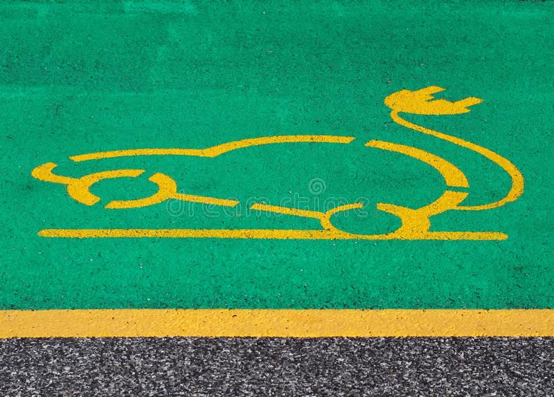 Electric car parking and charging sign. Yellow electric vehicle with plug painted on green background in the asphalt stock photos