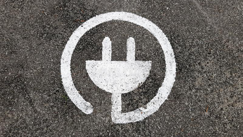 Electric charger symbol for cars, in a public parking.  stock photos
