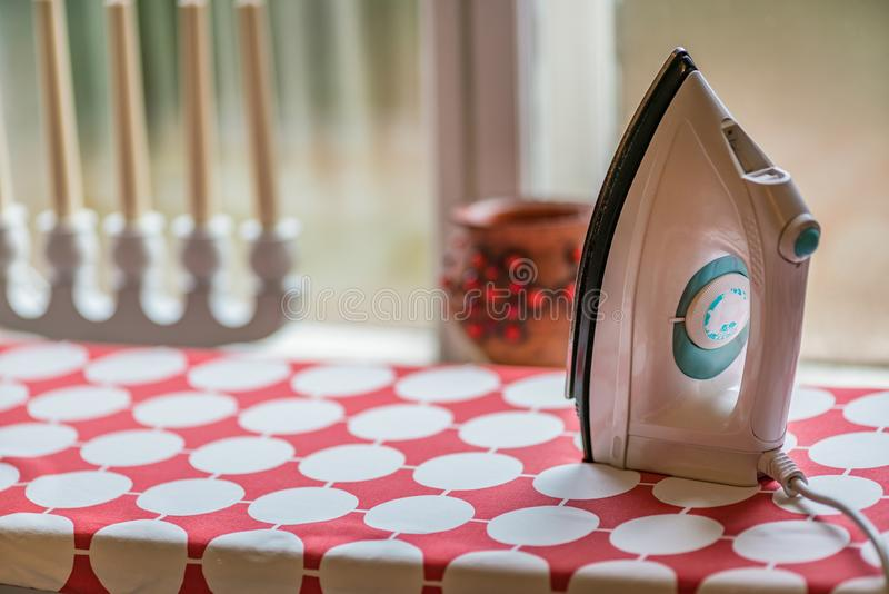 Electric clothes iron on the ironing board. Picture of Electric clothes iron on the ironing board stock photo