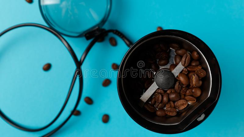 Electric coffee grinder with roasted coffee beans on the kitchen table with blue tabletop. Top view stock photo