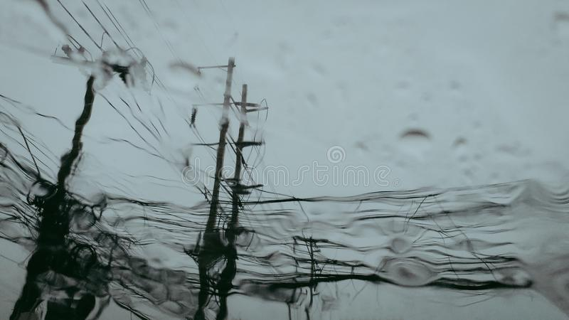Electric concrete poles with a wires when look from the window of the car,blue sky in the rainy day. royalty free stock images