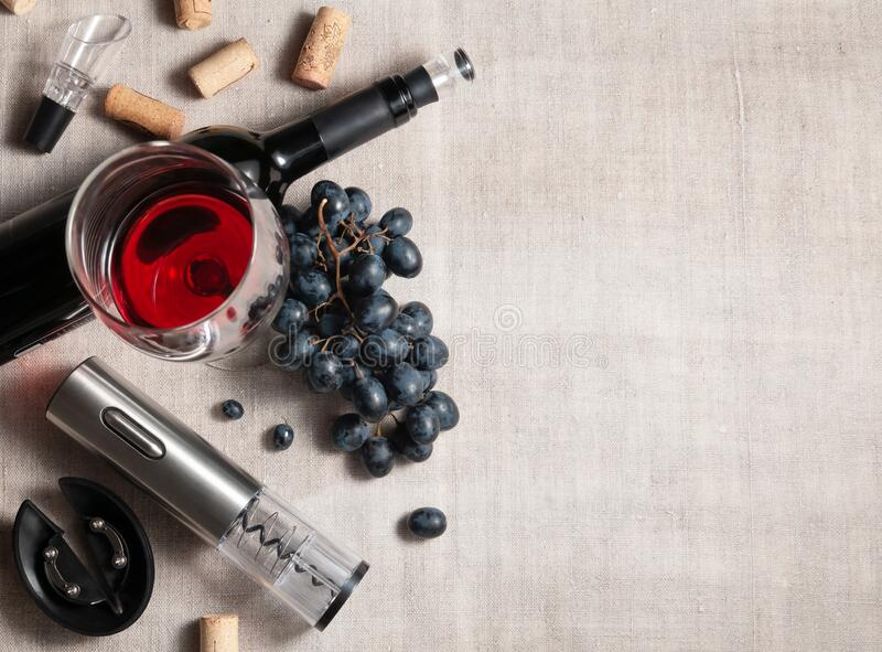 Electric corkscrew in steel gray. On a gray linen background. Near a glass, several corks, a bunch of grapes and a bottle of wine. Place for text royalty free stock photography