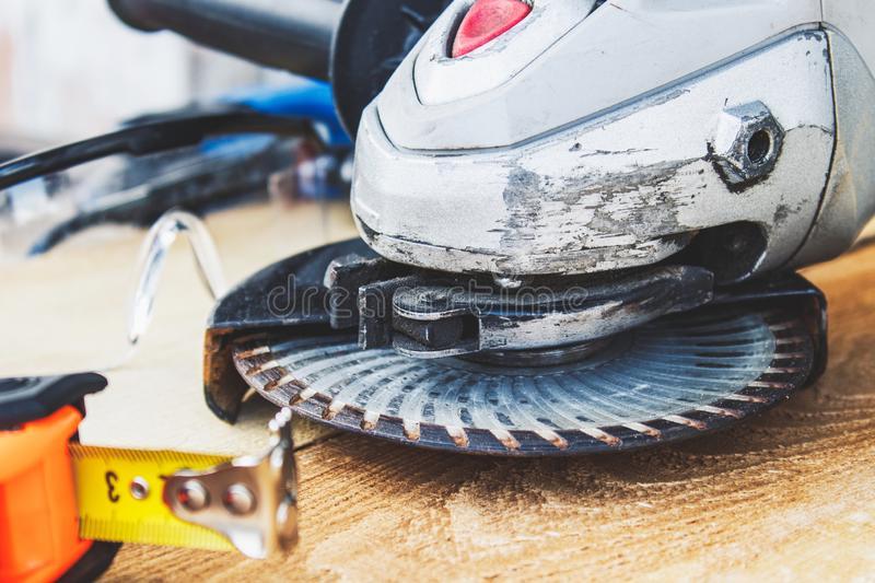 Electric cutting and grinding machine. Angle grinder with abrasive disc on wooden boards royalty free stock images