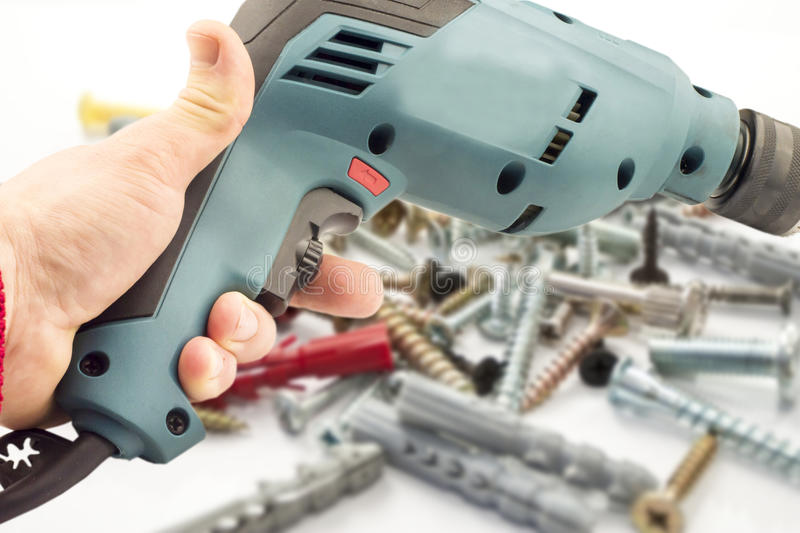 Electric drill in hand. Against the background of various bolts and dowels stock photo