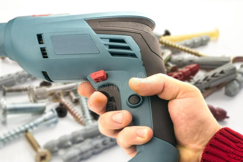 Electric drill in hand. Against the background of various bolts and dowels royalty free stock photography
