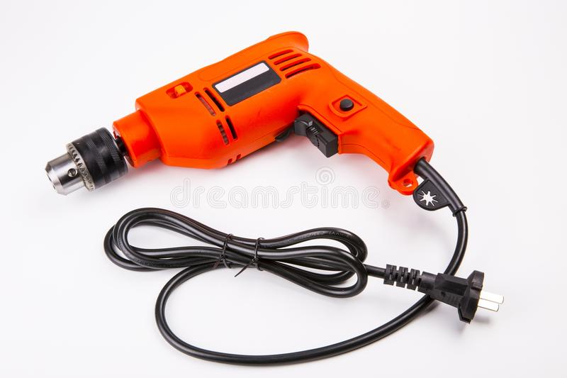 Electric drill. Orange electric drill with handle on white background royalty free stock photos