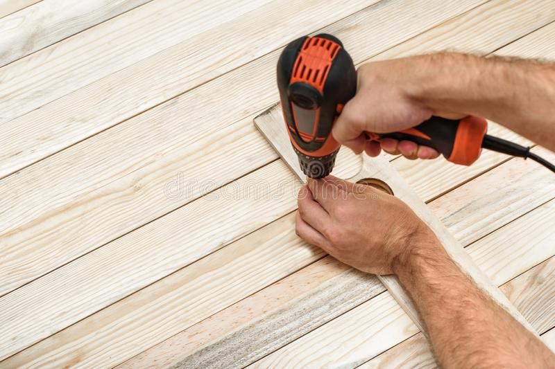 Electric drill screwdriver in male hand. Tightening screw, processing workpiece on light brown wooden table.  royalty free stock image