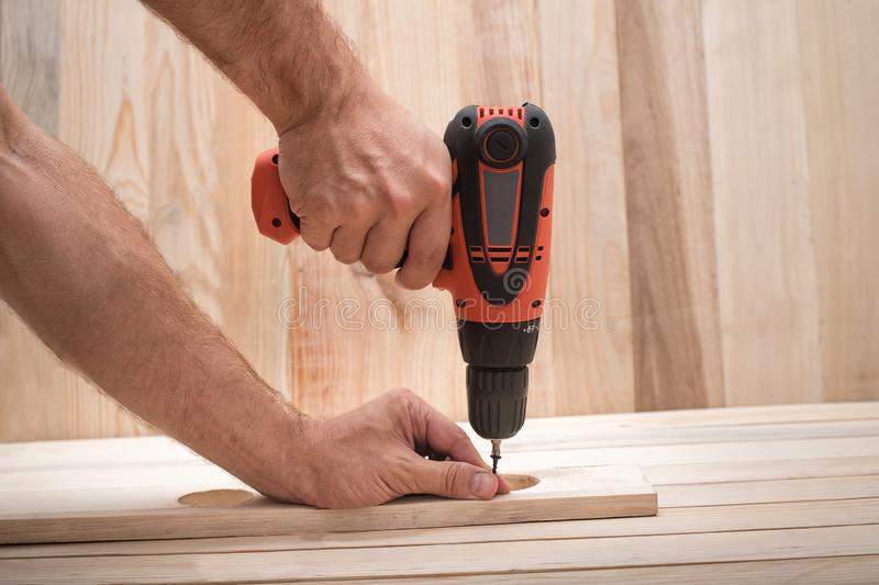 Electric drill screwdriver in male hand. Tightening screw, processing workpiece on light brown wooden table.  stock photo