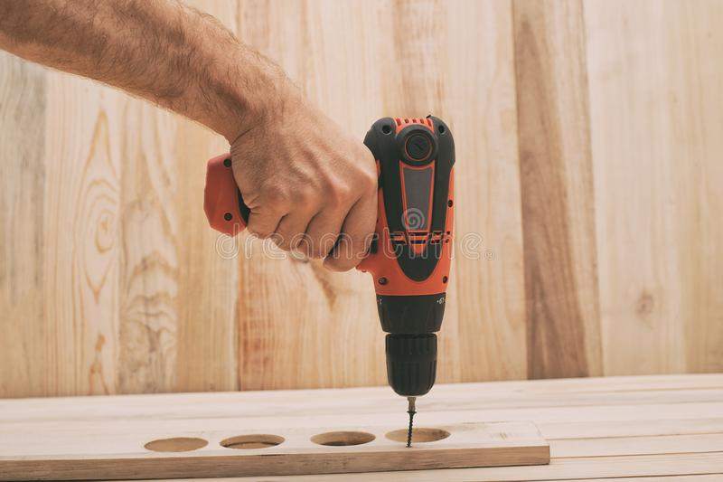 Electric drill screwdriver in male hand. Tightening screw, processing workpiece on light brown wooden table.  stock image
