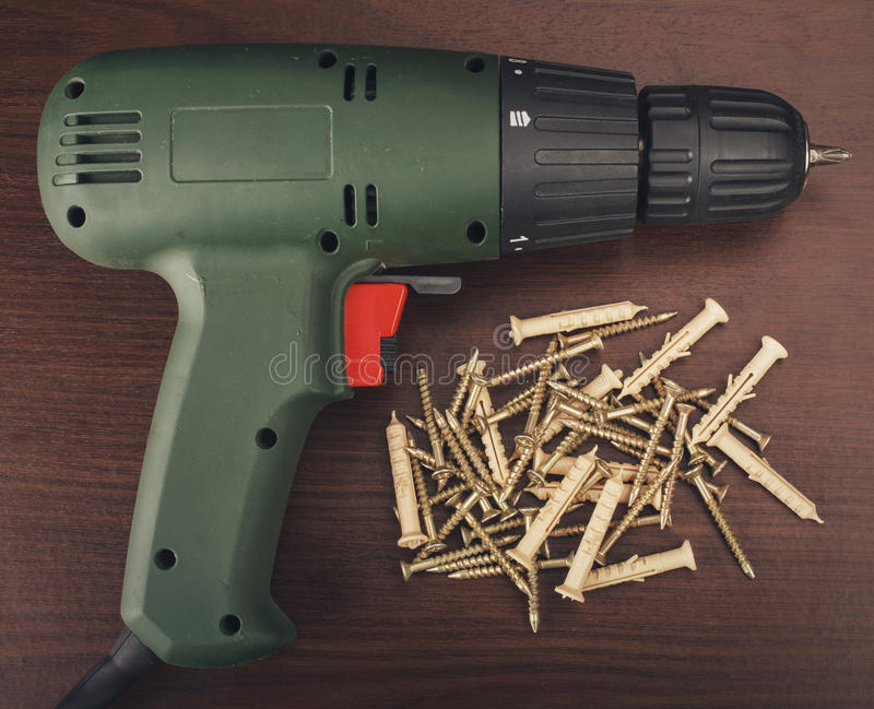 Electric drill and screws. Drill and large screws on a wood background stock image
