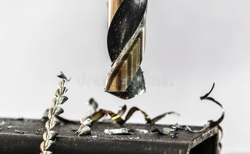 Electric drill to drill steel. Metal drilling closeup in metal workshop royalty free stock image