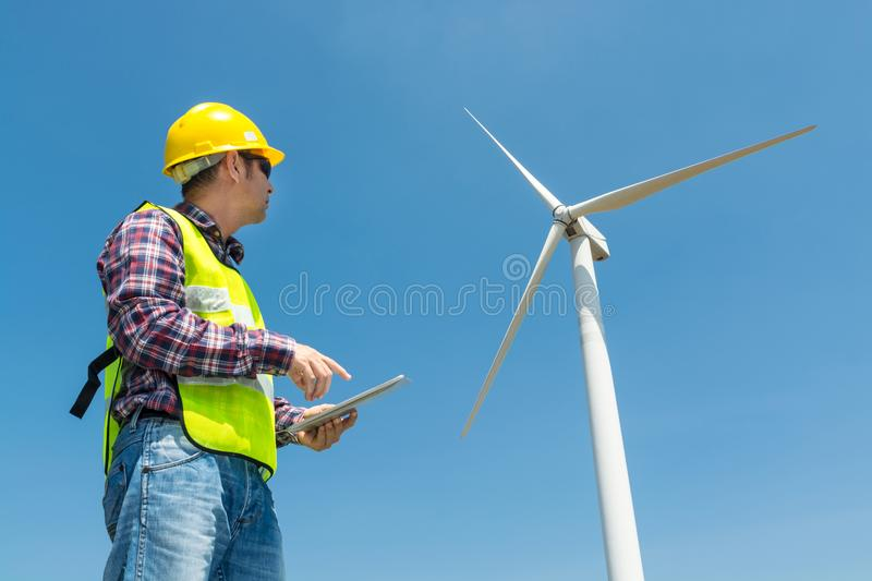Electric Engineer use Digital Wireless Tablet Device with Wind t. Urbine power Generator Tower Background as Green energy or Renewable Energy Technology Project stock photography