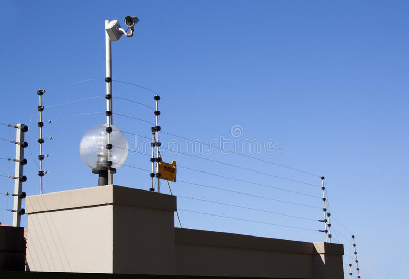 Electric fence and security camera atop boundary wall