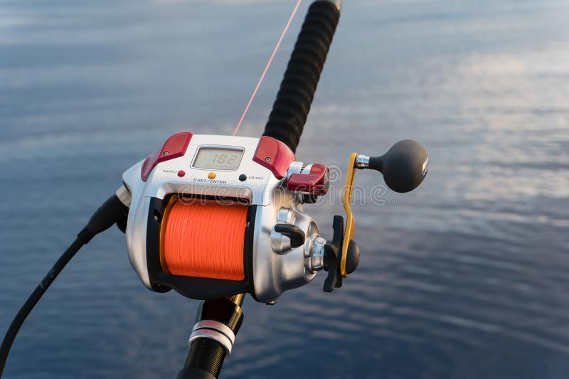 electric fishing reel mounted on a rod with sea in the background and orange line royalty free stock photos