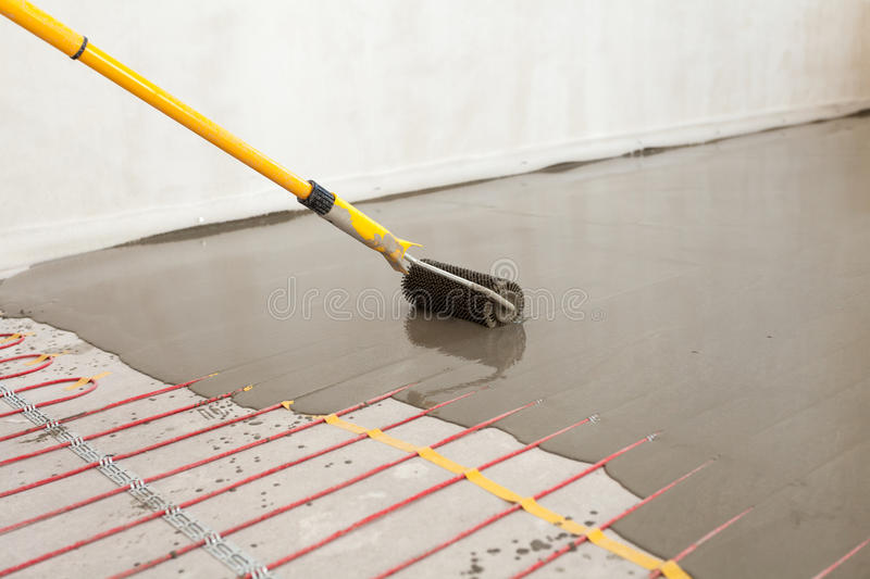 Electric floor heating system installation in new house. Worker align cement with roller. Electric floor heating system installation in new house. Worker align stock photography
