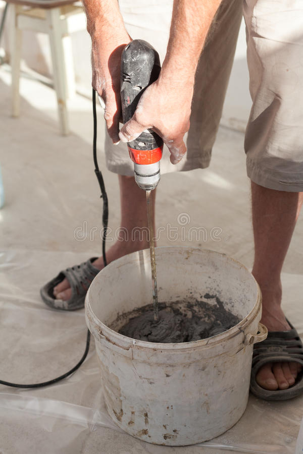 Electric floor heating system installation in new house. Worker use concrete hand mixer to prepare cement. Electric floor heating system installation in new stock photography