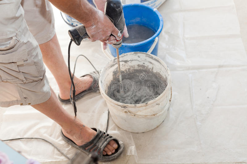 Electric floor heating system installation in new house. Worker use concrete hand mixer to prepare cement. Electric floor heating system installation in new stock photos