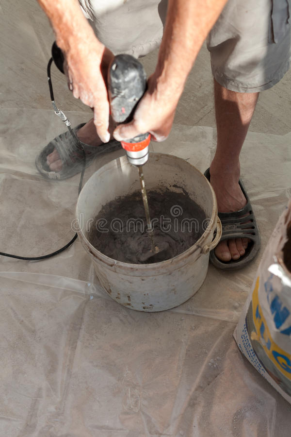 Electric floor heating system installation in new house. Worker use concrete hand mixer to prepare cement. Electric floor heating system installation in new royalty free stock photography