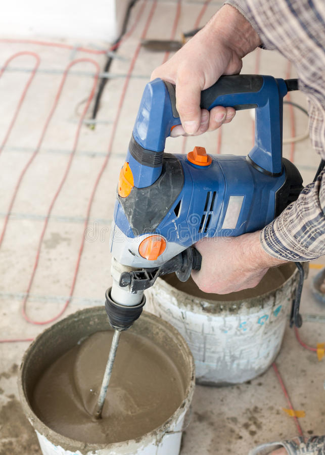 Electric floor heating system installation in new house. Worker use concrete hand mixer to prepare cement. Electric floor heating system installation in new royalty free stock photo