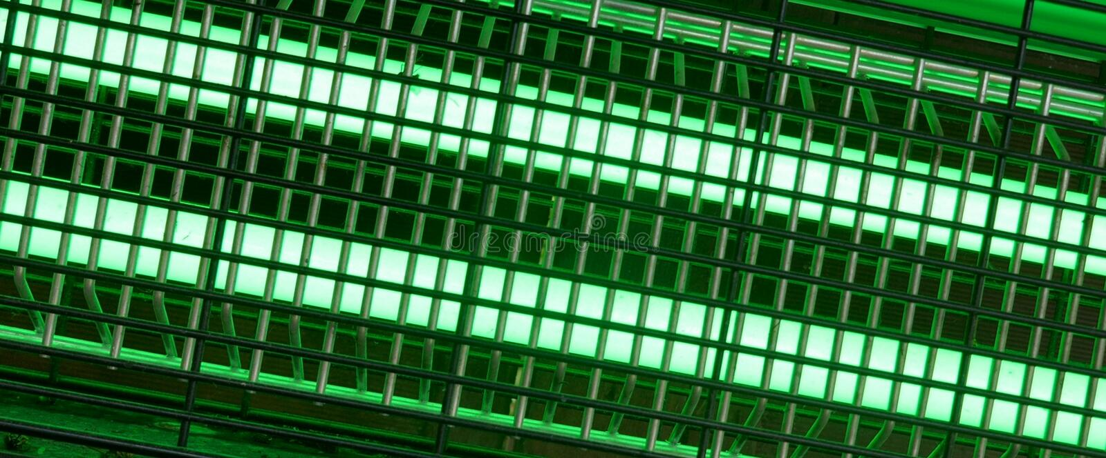 Bright green glowing UV lamp. Electric insect trap stock image
