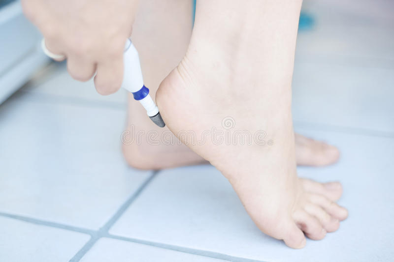 Electric foot scrubber being used in pedicure stock photos