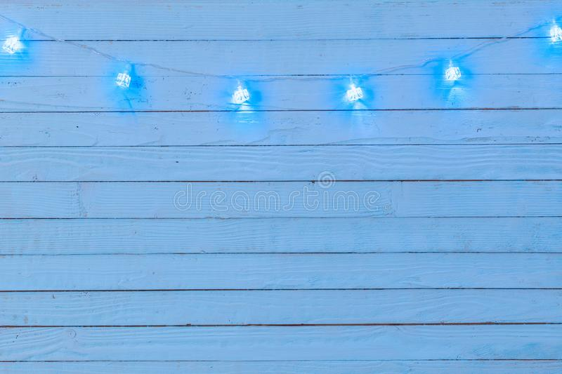 Electric garland with blue light bulbs in form ice cube on  wooden surface, Christmas and New Year background royalty free stock photos