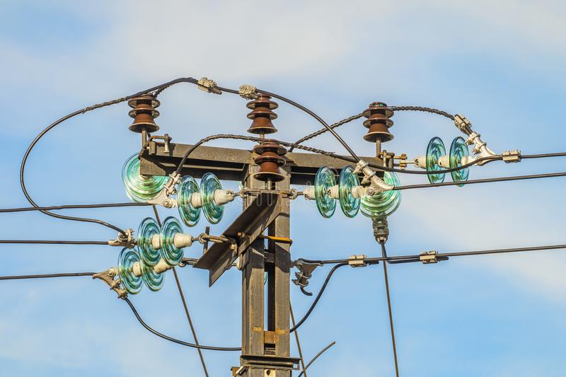 Electric garland of insulators and knots of connection electric cables. On top of a steel mast stock images