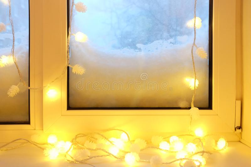 Electric garland on the windowsill at snowy winter evening stock images