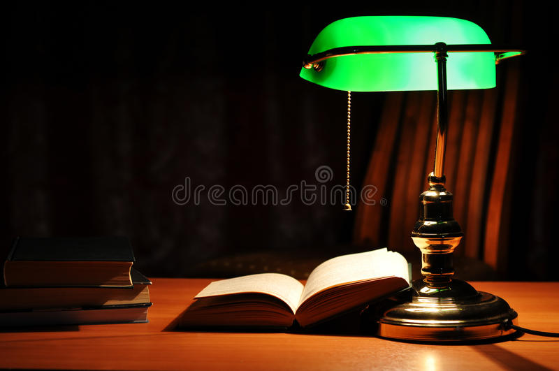 Electric green table lamp and book. Electric green table lamp and opened book stock photo