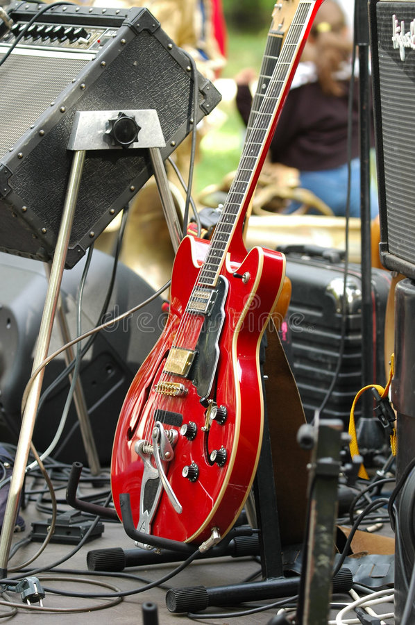 Electric Guitar. Red electric guitar on the stage among oher band equipment royalty free stock images