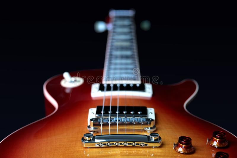 Electric Guitar Bridge Pick Up, Pots and Strings. Close up of electric guitar tailpiece, bridge pick up, volume and tone controls, body and neck stock image
