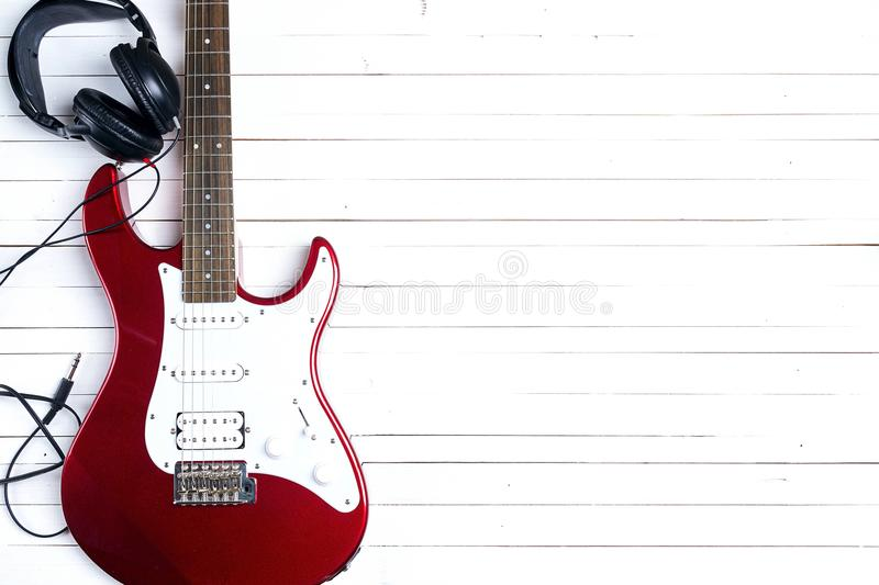 Electric guitar with headphones on white wooden table. Copy space. Electric guitar with headphones on white wooden table. Copy space, top view royalty free stock photo